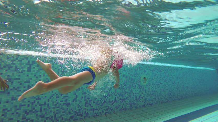 The teenager swims in the pool under the water.   Shutterstock HD Video #1016674738