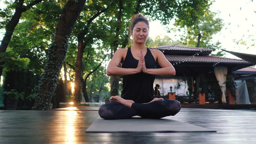 Pretty woman with oriental face practicing yoga, namaste gratitude mudra alone in tropical island. Girl in lotus pose. Religion, purity, resignation, spirituality concept. Padmasana.   Shutterstock HD Video #1016674921