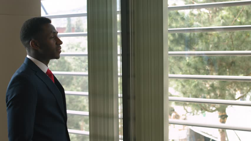Young afro american contemplative businessman stands in office and looks through big window at the city