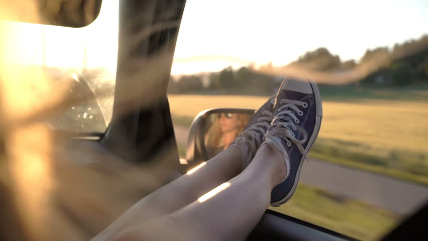A young redhead woman enjoys traveling in a car by sticking out her legs in an open window. Slow motion.