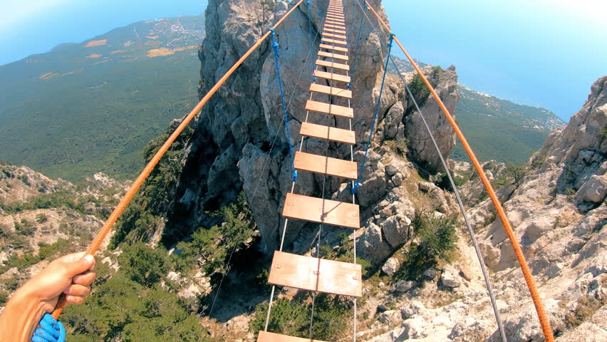 The mountains . Extreme sport . Crossing the rope bridge. The man slowly crosses the bridge. GoPro. | Shutterstock HD Video #1016703925