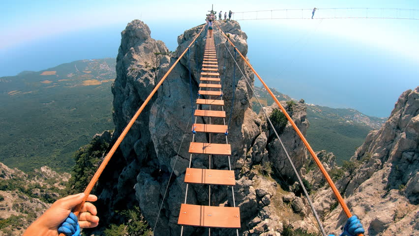 The rope bridge. Crossing over a suspension bridge in the mountains. Extreme sport. GoPro. | Shutterstock HD Video #1016703928