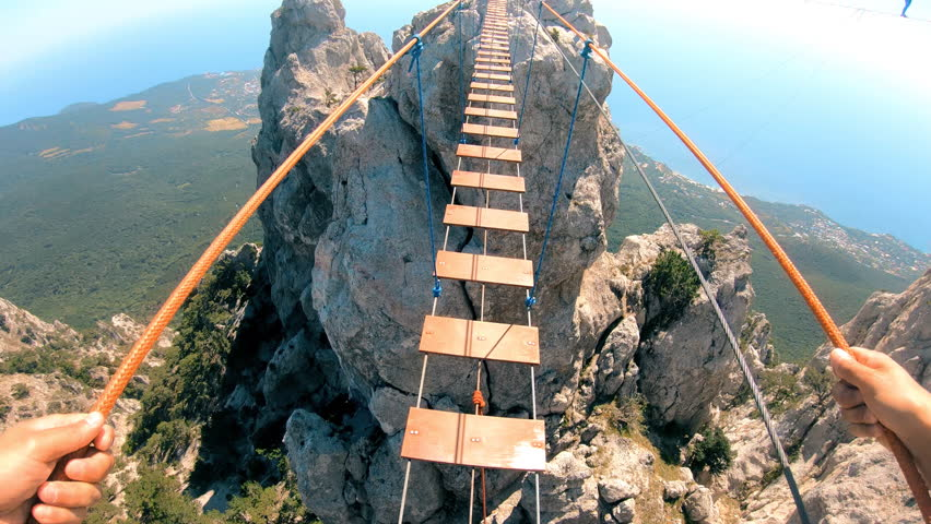 The rope bridge. Crossing over a suspension bridge in the mountains. Extreme sport. GoPro. | Shutterstock HD Video #1016703931