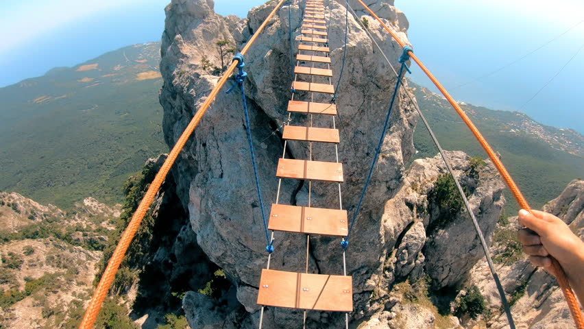 The rope bridge. Crossing over a suspension bridge in the mountains. Extreme sport. GoPro. | Shutterstock HD Video #1016703934