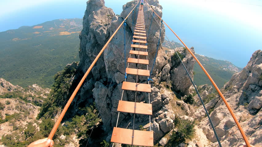 The mountains . Extreme sport . Crossing the rope bridge. The man slowly crosses the bridge. GoPro. | Shutterstock HD Video #1016703940