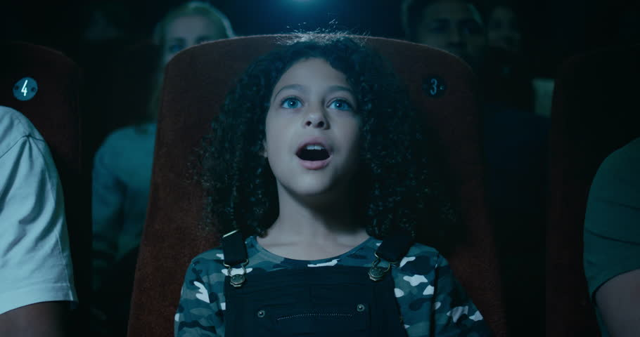 Captivated little girl in a movie theatre is awestruck by a incredible moment on screen