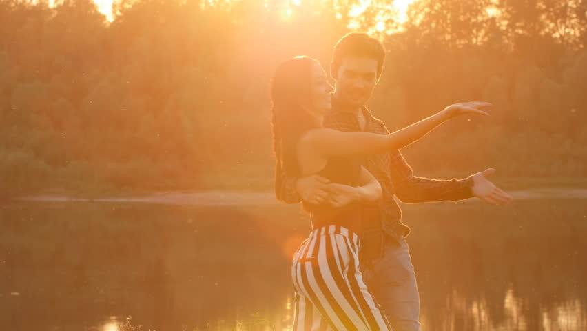 Couple dancing bachata at sunset