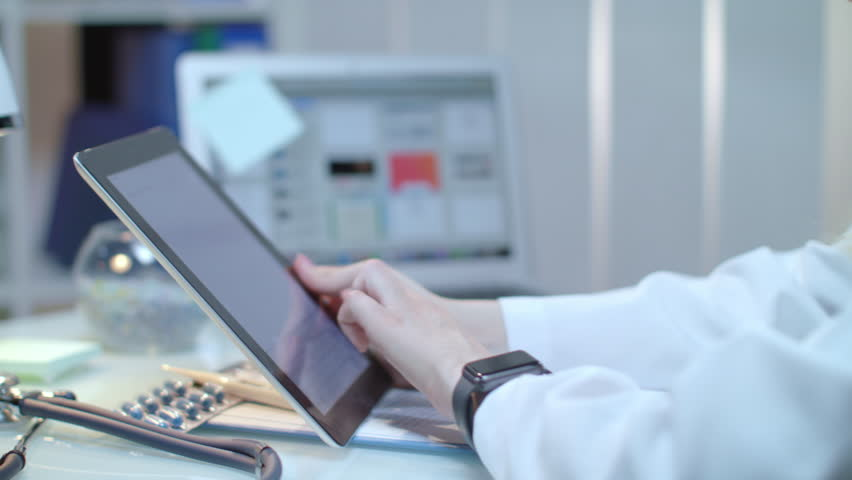 Female doctor using tablet at medical workplace. Nurse using tablet pc. Close up of medical specialist touch tablet screen. Woman doctor working with ipad. Modern technology for medical workers