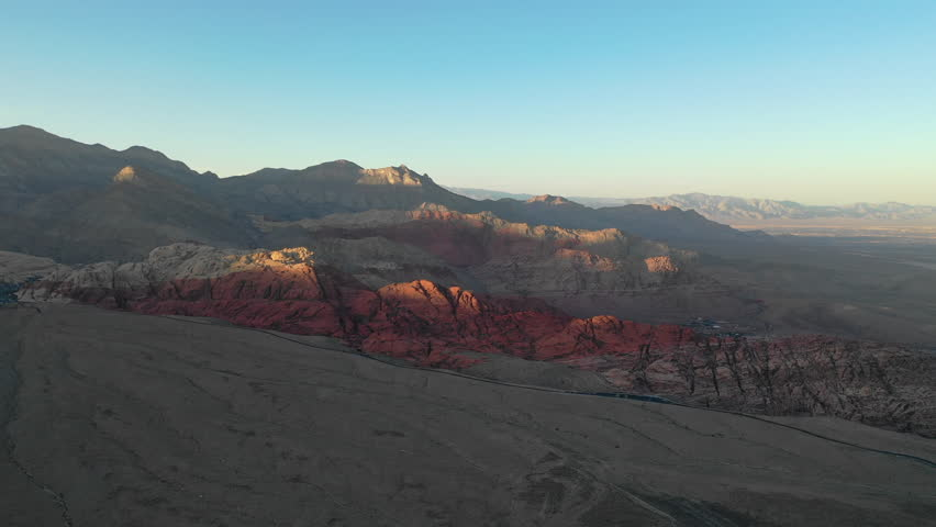 Soft evening light shines on the Red Rock Canyon National Conservation Area, located just outside of Las Vegas, NV. Its massive red rock geologic formations are popular for hiking and climbing. | Shutterstock HD Video #1016750284