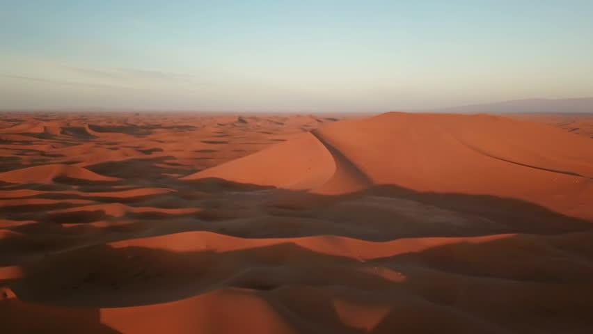 Flying over sand dunes in Sahara desert at sunrise, Africa #1016762293
