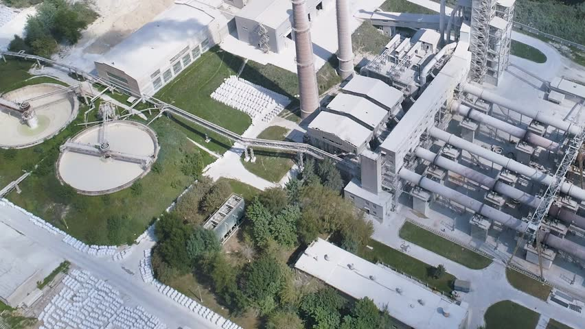 Cement factory, industrial enterprise. The smoking factory chimney. Shooting from the drone, smooth flight over the plant. | Shutterstock HD Video #1016784202