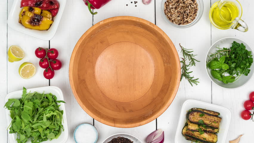 Fresh salad with grilled vegetables in wooden bowl with food ingredients on white wooden rustic table. Top view, 4k stop motion animation. | Shutterstock HD Video #1016789056