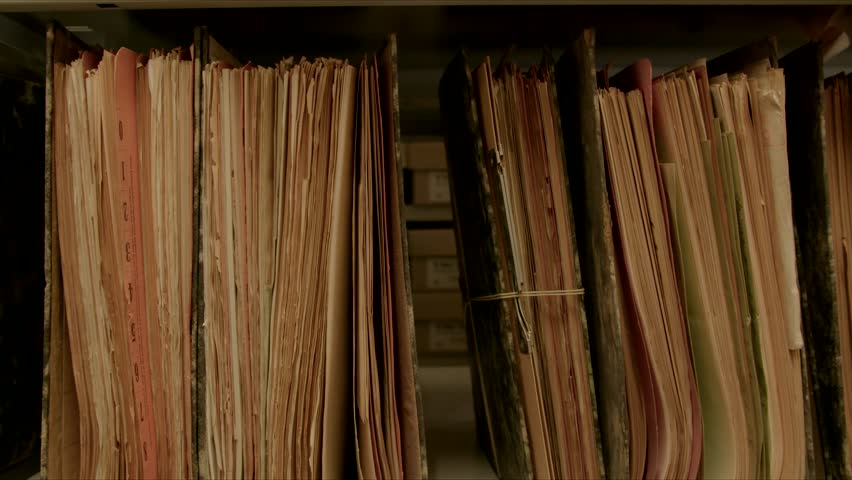 Camera movement along a file shelf. The files are old, the paper is yellowed. The image can be used for the integration of archive texts in films and reports. Thanks to the 50 frames it can be slowed  | Shutterstock HD Video #1016795260