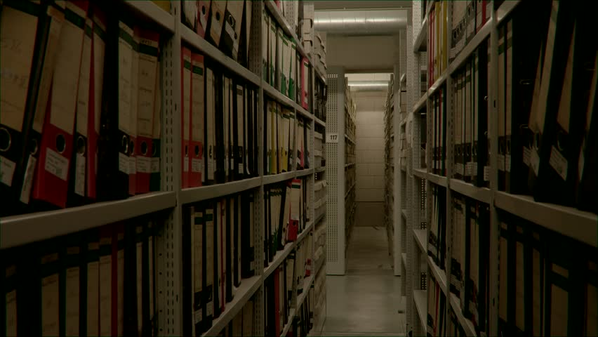 Slow camera movement between two archive shelves filled with folders. The image can be used for the integration of archive texts in films and reports. Thanks to the 50 frames it can be slowed down.  | Shutterstock HD Video #1016795266