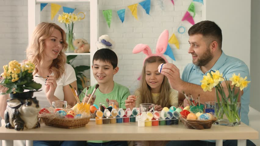 Funny family with kids wearing bunny ears painting eggs on Easter day | Shutterstock HD Video #1016797882