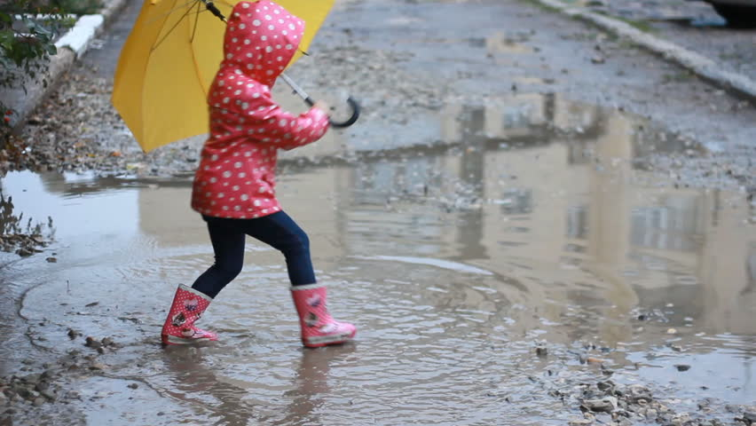 Funny child girl jumping and playing in puddles in rainy weather under an umbrella