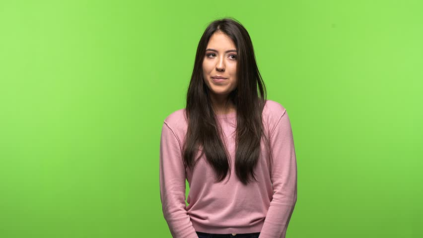 Young pretty girl on green chroma key background doubting and confused, thinking of an idea or worried about something