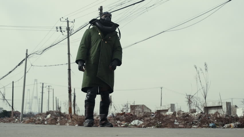 Postapocalypse, lonely man walks amid garbage dump and abondoned town | Shutterstock HD Video #1016811088