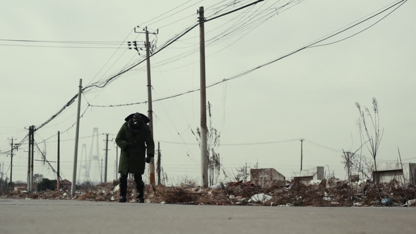 Postapocalypse, lonely man walks amid garbage dump and abondoned town | Shutterstock HD Video #1016811109