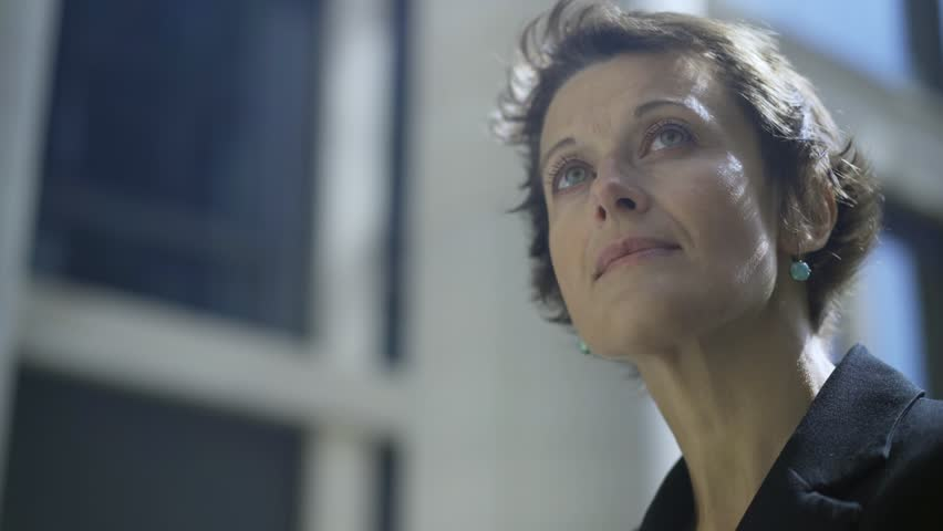 Close-up panning shot of beautiful middle aged woman with short hair and green eyes looking away in street being deep in thought Royalty-Free Stock Footage #1016821702