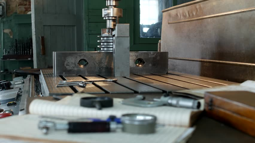 A private workshop for working with metal parts, in the background a drilling machine drills a hole in the pulley, on the table lie measuring instruments, mensuration | Shutterstock HD Video #1016826571