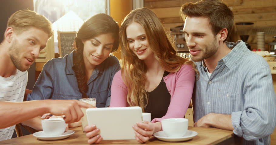 Group of Caucasian friends using digital tablet in cafe 4k #1016828017