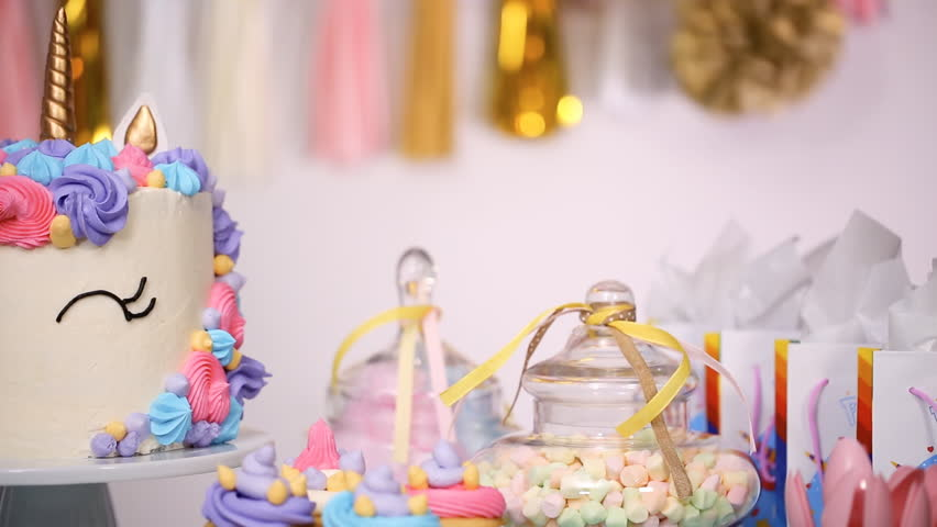 Close up of little girl's birthday party table with unicorn cake, cupcakes, and sugar cookies. | Shutterstock HD Video #1016838523