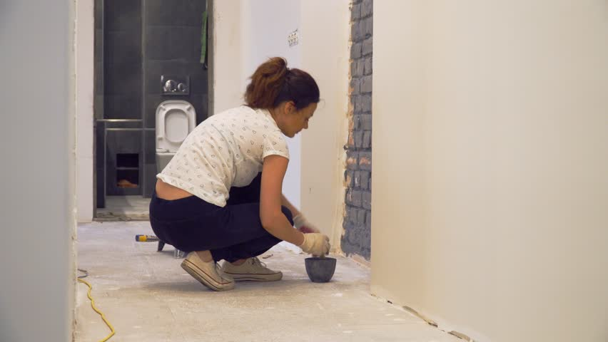 Squatting girl paints brick wall in gray using brush. Renovation in the corridor of empty apartment with white walls. Bathroom in the background. | Shutterstock HD Video #1016876536