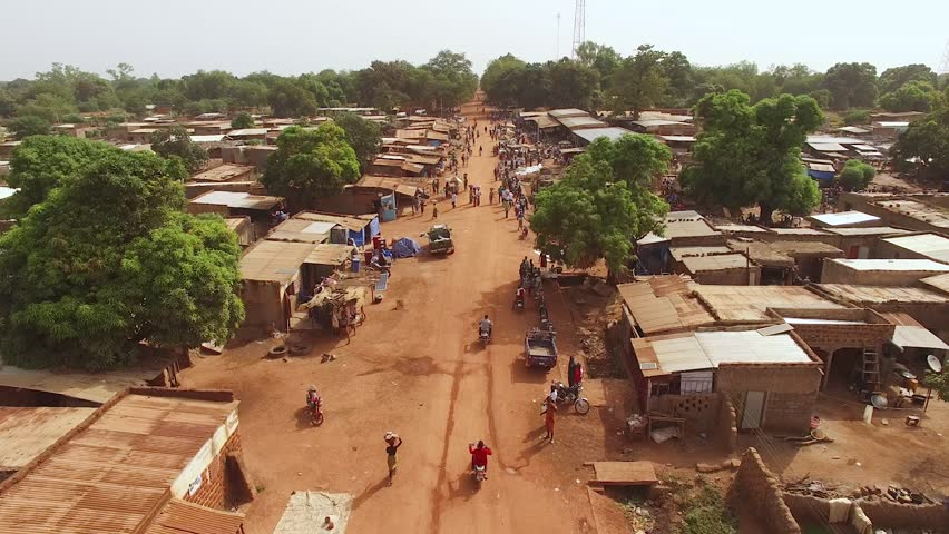 Flying along a busy street over an open-air market on a hazy day in West Africa