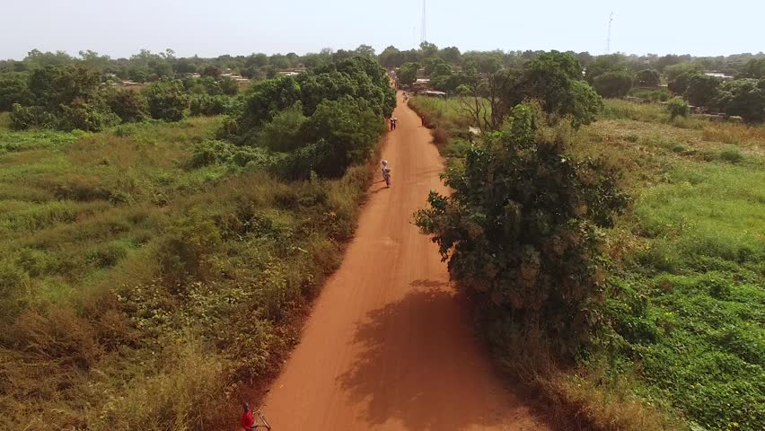 Rising aerial shot revealing a small West African town on a hazy day with radio towers in the background