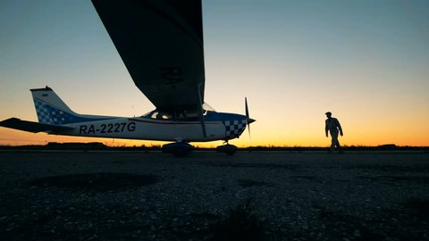 Person standing near his airplane on a sunset background. Small aviation concept.