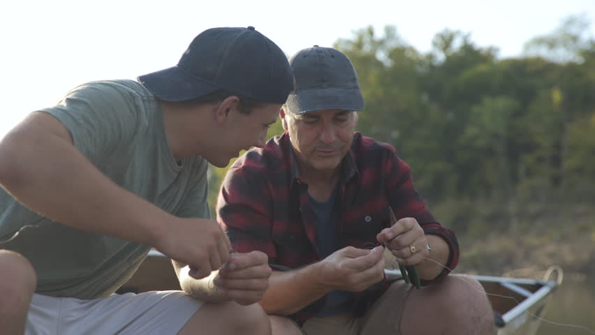 Dolly shot of father guiding son in adjusting fishing rods while sitting on boat at forest