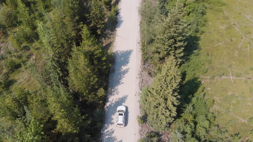 Aerial Drone Shot Flying Above Car Driving On Dirt Road In Forest