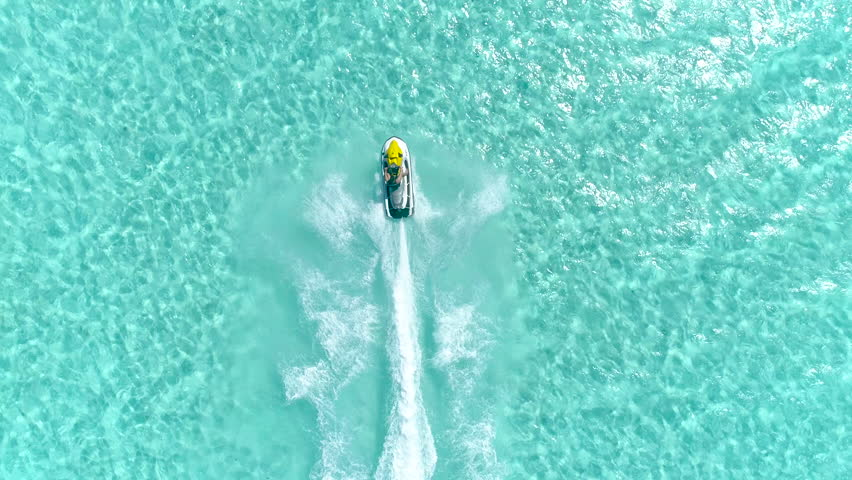 Aerial - Epic shot of a jet ski racing on a crystal clear water. Adult male enjoying summer vacation in Bora Bora speeding on a jet ski