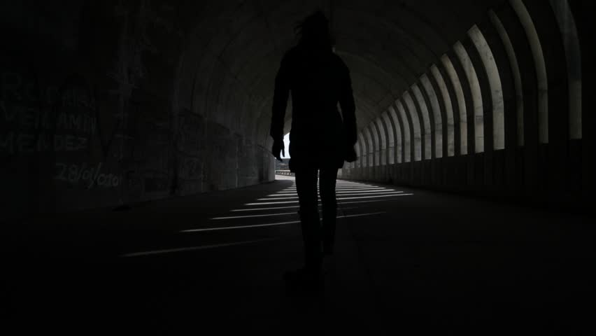 Hand held camera woman walking over street going out a brutalist concrete tunnel. Lights and shadows rithms made by windows, openings, within the tunnel. Flares of sunlight. Argentina, Mendoza