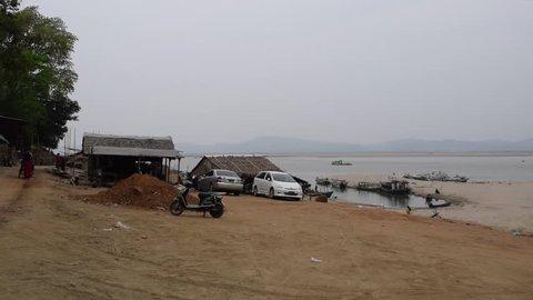 Irrawaddy River, Old Bagan, Myanmar - 08 April 2018: Life at the Harbor, Boy Walks by Carrying Water, Pan Shot