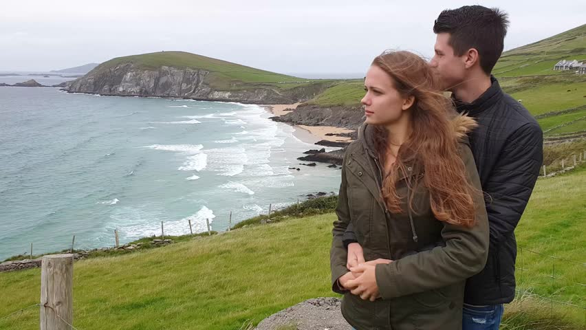 Young couple in love is impressed by the amazing scenery at the Irish west coast | Shutterstock HD Video #1016953246