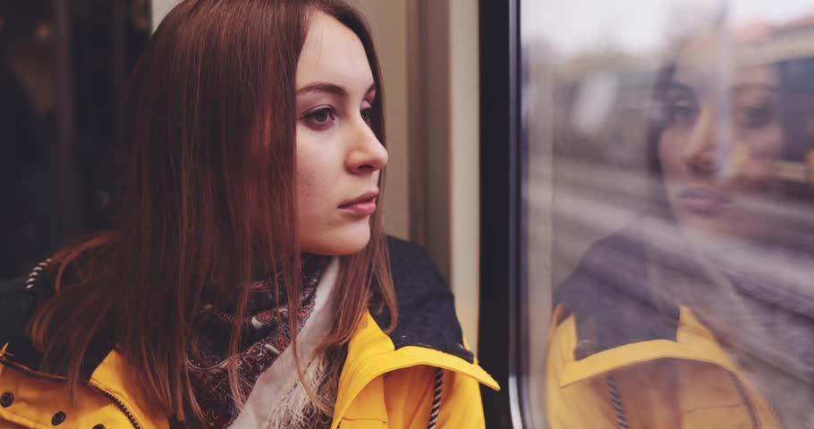 Sad Young Woman Looking Out of a Train Window. SLOW MOTION 4K. Tired, depressed girl thinking of something seating near the window in city train during her daily commute.