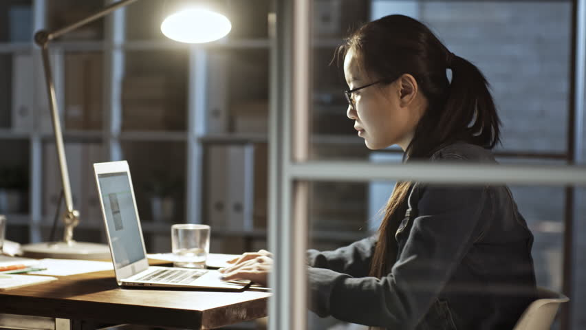 Professional asian business woman in eyeglasses sitting at table in dark office and typing on computer   Shutterstock HD Video #1016968471