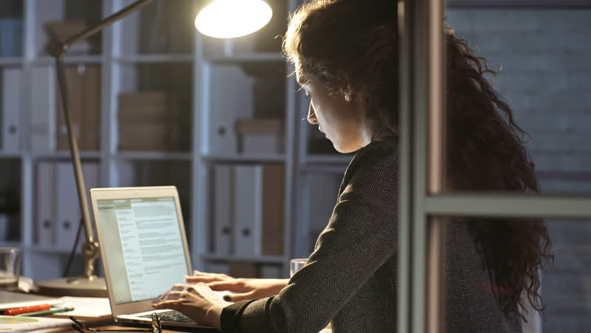 Young female journalist writing an article on laptop while working alone in office at night