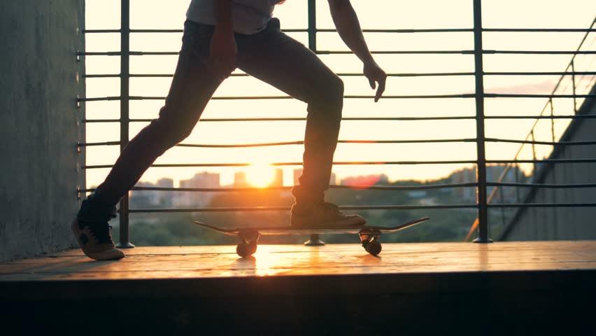 Man starts riding a skateboard on a city background, slow motion. #1016984383