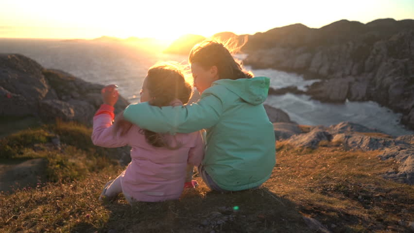 Two little girls admire the sunset or dawn sitting on the coastal rocks on the northern beach. They take care of each other, covering themselves from the strong wind and hugging. Slow motion | Shutterstock HD Video #1016992522