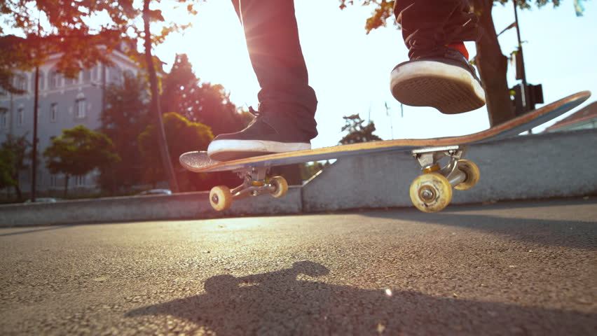 SLOW MOTION, LENS FLARE, CLOSE UP: Unknown skateboarder jumps and lands a cool trick while riding on concrete sidewalk in sunny city. Cinematic view of skateboard flipping in air under man's feet Royalty-Free Stock Footage #1016993902