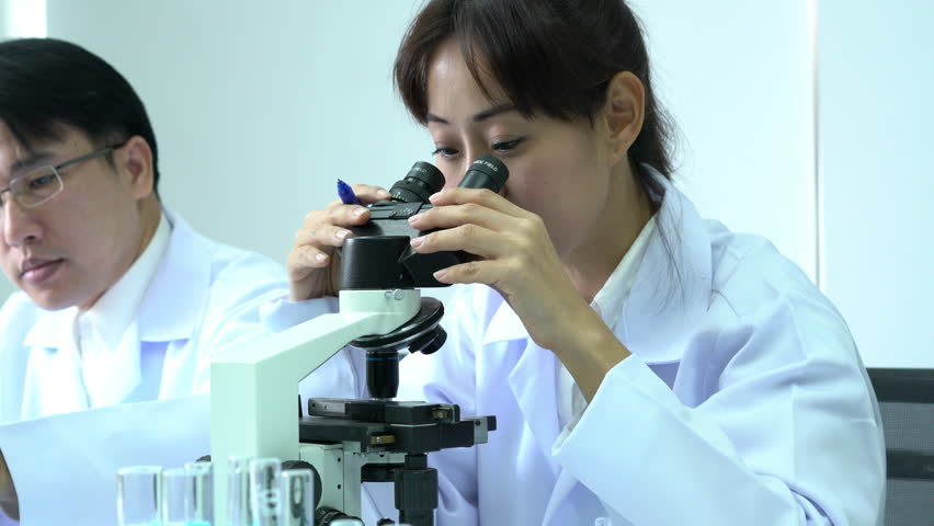 Scientist female is looking through microscope with colleagues working in modern laboratory or medical center together. Concept of science, testing development and lab industry.