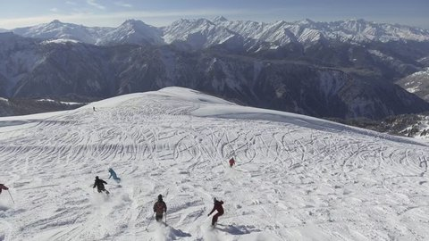 Group of skiers and snowboarders in colorful costumes are gliding down off of hill top covered with snow and surrounded by spectacular mountains on winter sunny day.