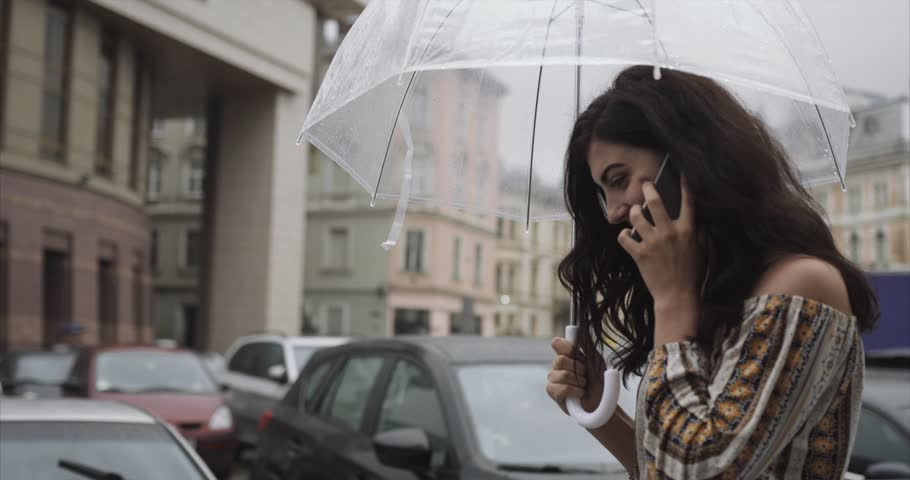 Walking under the rain. Charming young brunette woman in dress with open shoulders walks with umbrella along the street of an old town and talks on her phone | Shutterstock HD Video #1017034927