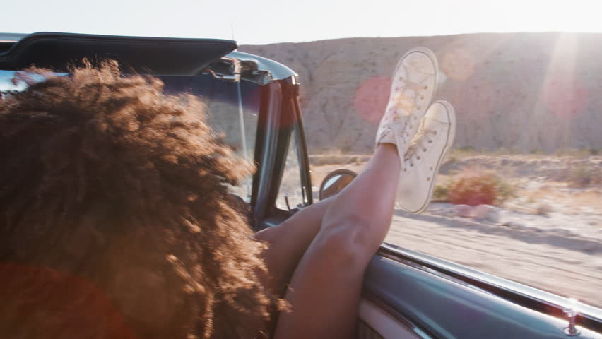 Young woman with legs sticking out of moving car, back view