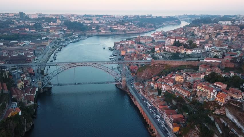 Flying over Dom Luis I iron bridge across Douro river early morning in Porto, Portugal. Aerial view of the old city center.  | Shutterstock HD Video #1017037834