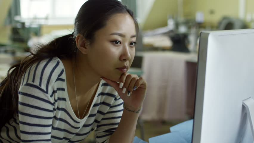 Medium shot of concentrated young Asian woman using desktop computer at work and thinking | Shutterstock HD Video #1017040474