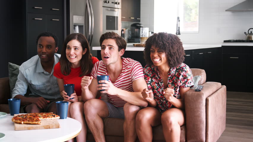 Four young adult friends watching sports on TV celebrating